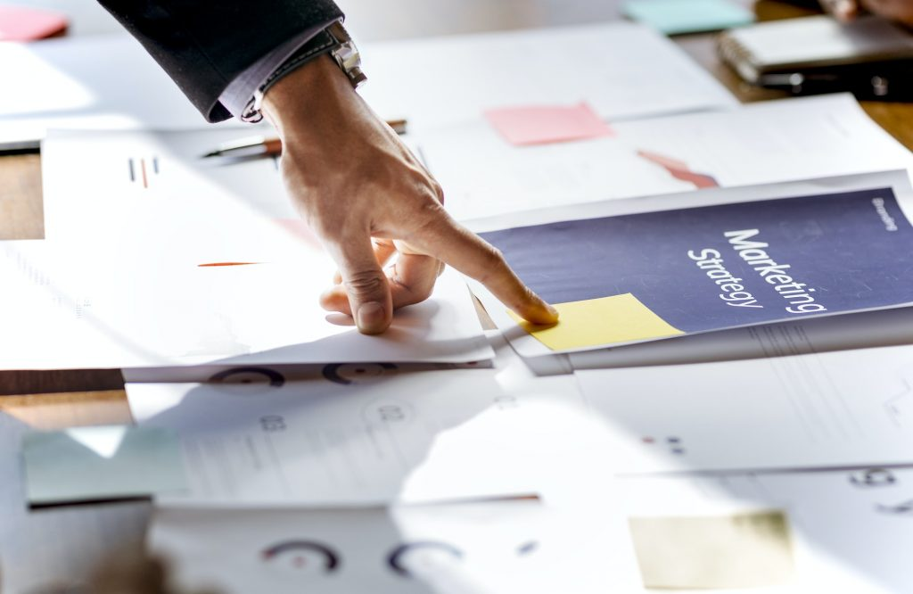 Hand pointing on a marketing strategy document