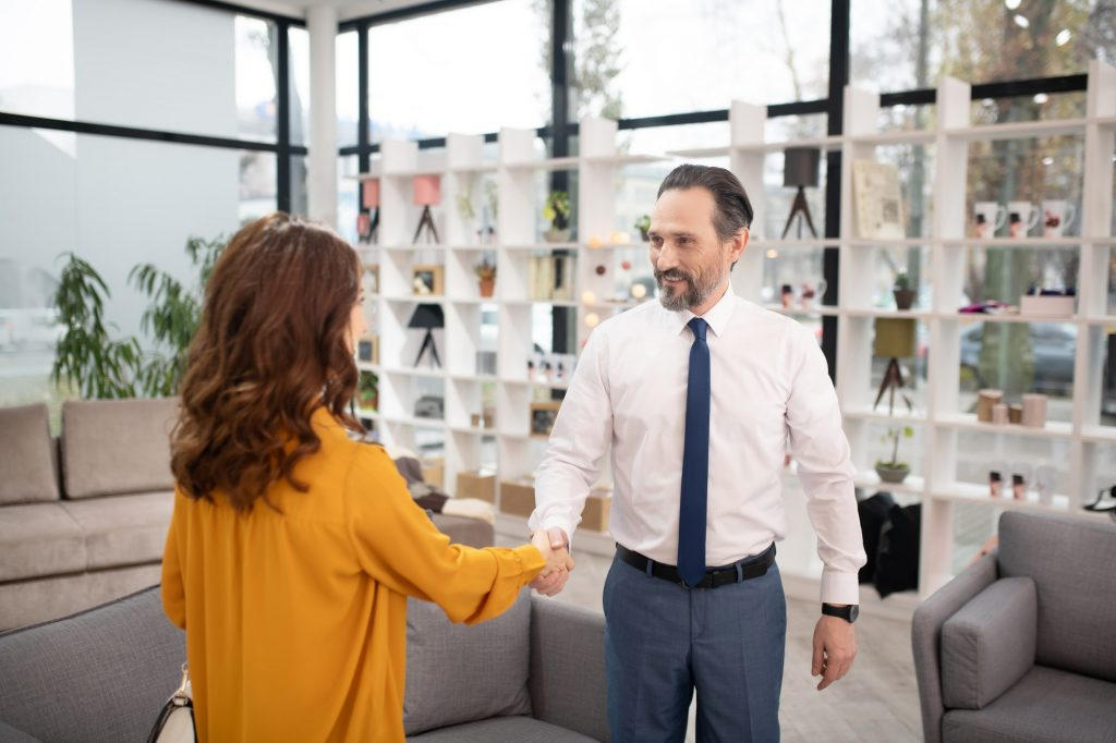 Manager in tie and white shirt meeting a new customer