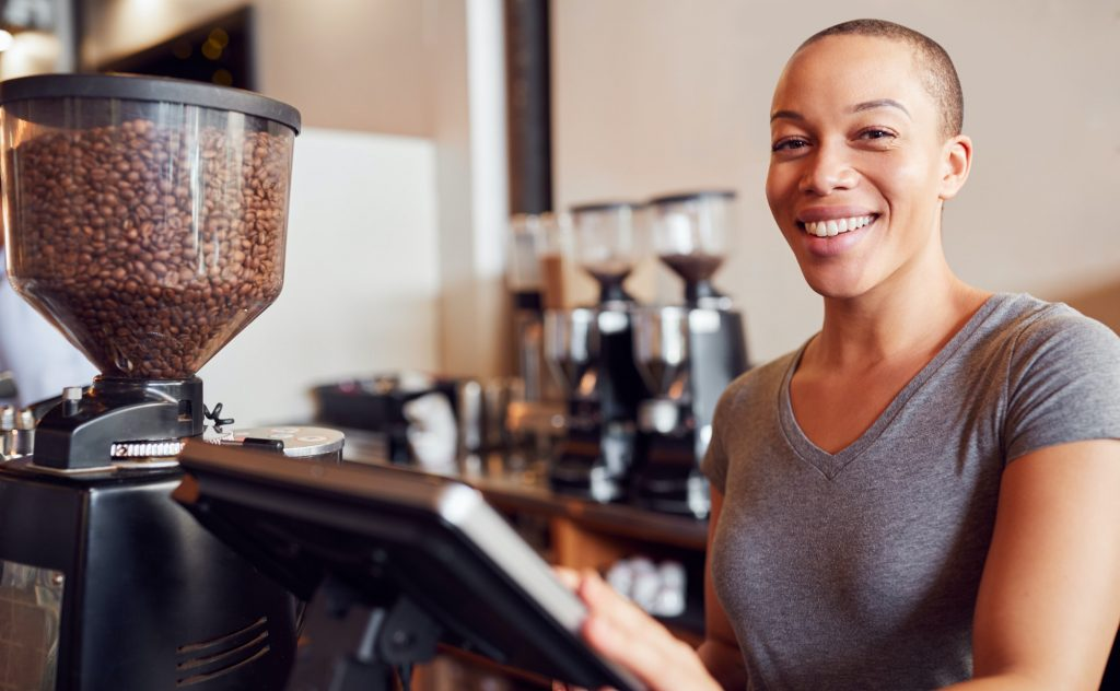 Portrait Of Female Coffee Shop Owner Standing At Sales Desk