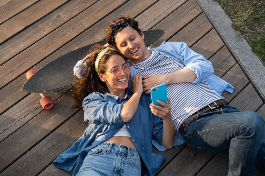 Cheerful couple relax outdoors use smartphone happy smiling lying on longboard browse social media