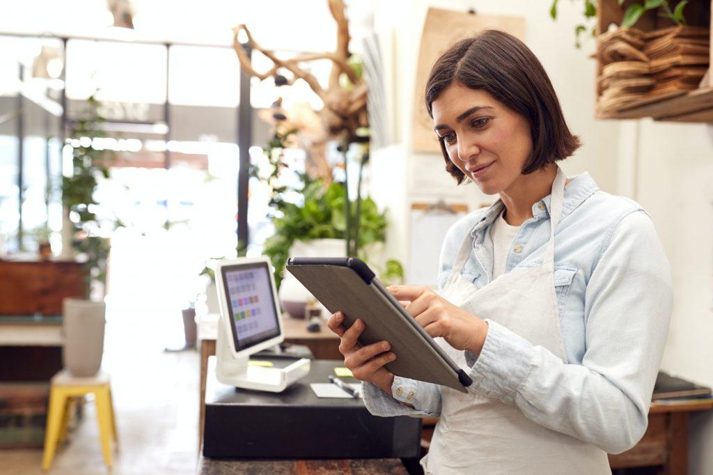 Female Owner With Digital Tablet Standing Behind Sales Desk Of Florists Store